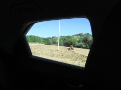A tractor at work from the back car window
