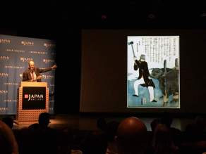Dr. Botsman showing a Japanese depiction of an American slaughtering a cow. © Kaori Mahajan for WhereNYC
