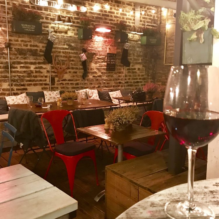 Red wine in the foreground with empty tables and chairs behind and Christmas stockings on the wall