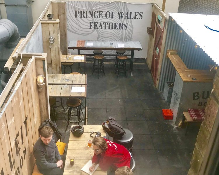 sign that says 'prince of whales feathers'  empty tables and chairs