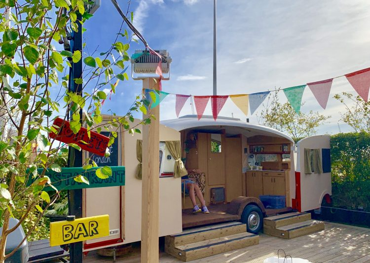 caravan with doors open  and signs to to the bar in yellow