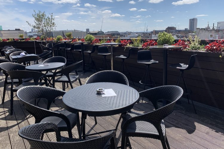 Rooftop bar in oxford street empty table and chairs