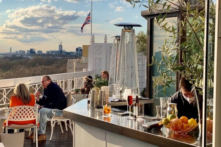 Bartender making drinks behind a bar at the Dorchester new rooftop bar view of london