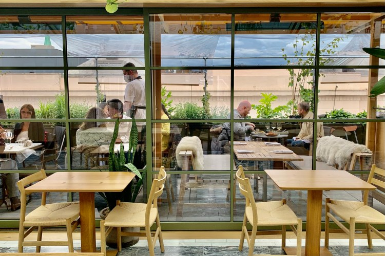 2 table and chairs in front of glass doors that show the rooftop bar