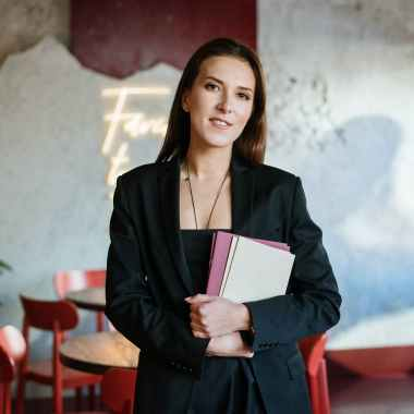 woman in black blazer holding white paper