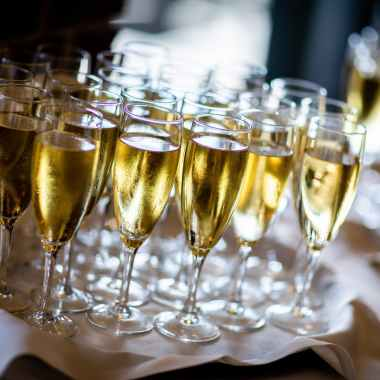 clear wine glasses with gold liquid on white cloth covered table