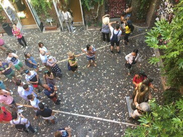 Courtyard at Casa di Giulietta; people posing with the Juliet statue for good luck in love