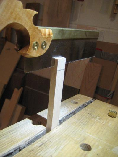 Making the center guides using hand tools. Here I'm using a dovetail saw to rip away part of the half lap.