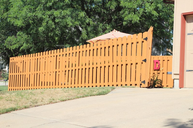 How to stain a fence: This post details what steps and materials we took and used to transform the look and condition of our wood fence. We did pressure washing, spray painting, painting, and more. The project was inexpensive, easy, and dramatic in effect. Anyone could do it! Click here to read more and get started on your fence!