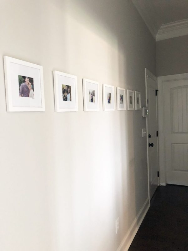 This family photo wall displays a simple arrangement of gallery-style images that shows the family in one photo each year. This hallway collage provides sentimental decor that will be meaningful for years to come. Click here for a full list of sources so that you can get going on creating this affordable, fast, and treasured wall for your family to enjoy.