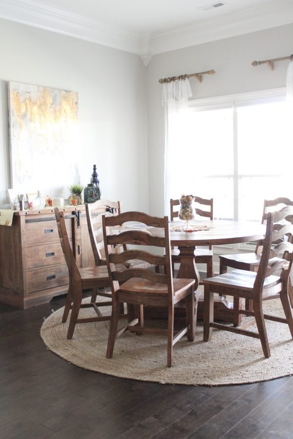"We love this family kitchen eating area! In this post, I share details about our new 54"" round kitchen table, our 8' round jute rug, matching sideboard, curtains, rods, and more. Gather new ideas and inspiration for big or small kitchens. This specific round table area is near a window with a big wall for decorating. Click here to read more and get links to resources."