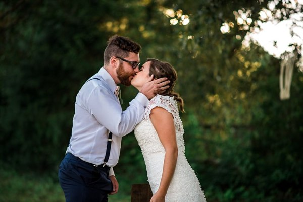 First Look Bride Lace Bridal Gown With Buttons Soft Curls Hairstyle Groom Navy Pants Suspenders Cream Bow Tie Glasses Kiss Trees Grass Ethereal Boho Wedding Ideas http://perfectcapturephoto.com/