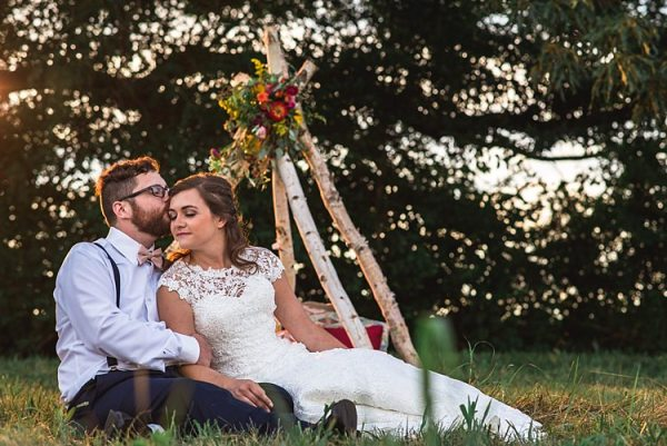 Bride Lace Bridal Gown With Buttons Groom Navy Pants Suspenders Cream Bow Tie Tee Pee Multicoloured Florals Pink Yellow Red Cushions Trees Grass Ethereal Boho Wedding Ideas http://perfectcapturephoto.com/