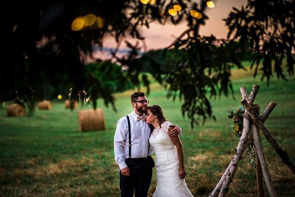 Bride Lace Bridal Gown With Buttons Groom Navy Pants Suspenders Cream Bow Tie Teepee Multicoloured Florals Grass Hay Bales Trees Sunset Ethereal Boho Wedding Ideas http://perfectcapturephoto.com/