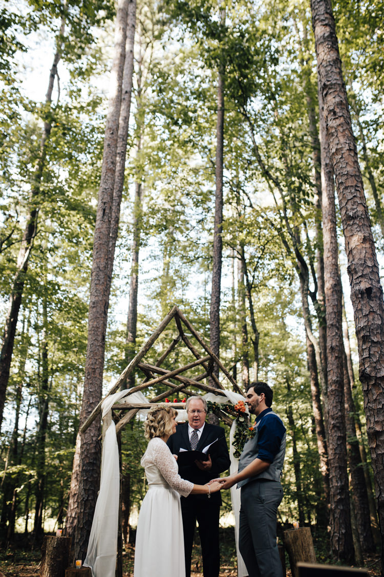 Outdoor Ceremony Bride Handmade Lace Bridal Gown Groom Grey Vest Pants Navy Blue Shirt Orange Tie Decorated Wooden Arbour Fresh Florals Celebrant Adventure Inspired Woodland Wedding North Carolina http://www.amandasuttonphotography.com/