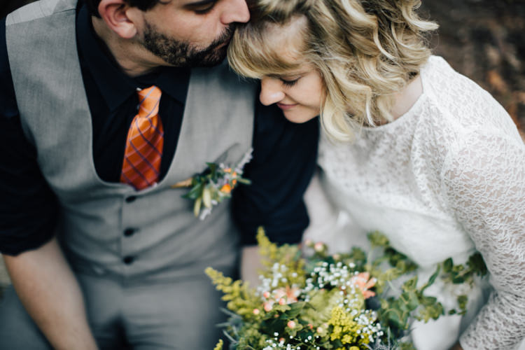 Outdoor Ceremony Location Bride Handmade Lace Bridal Gown Bouquet Orange Florals Gypsophila Groom Grey Vest Pants Navy Blue Shirt Orange Checkered Tie Buttonhole Orange Florals Succulent Adventure Inspired Woodland Wedding North Carolina http://www.amandasuttonphotography.com/
