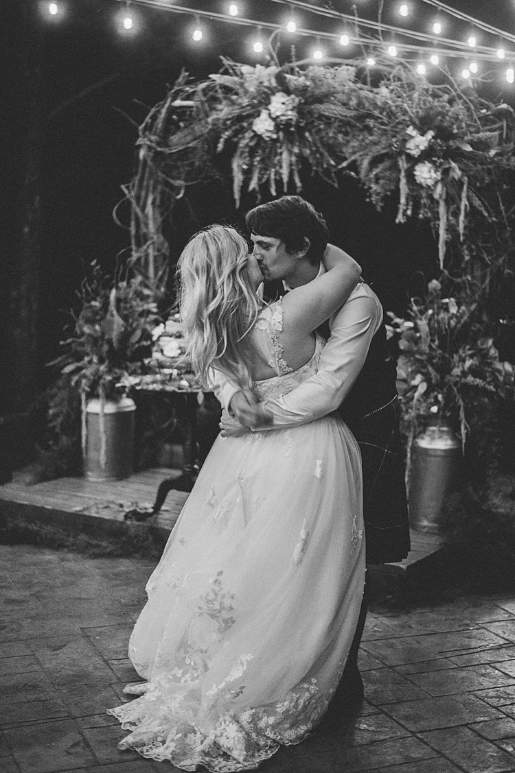 Bride Groom Kiss Embrace Lace A Line Gown Cap Sleeve Outdoors Festoon Lighting Archway Greenery Whimsical Woods Wedding Barn Ohio http://www.connectionphotoblog.com/