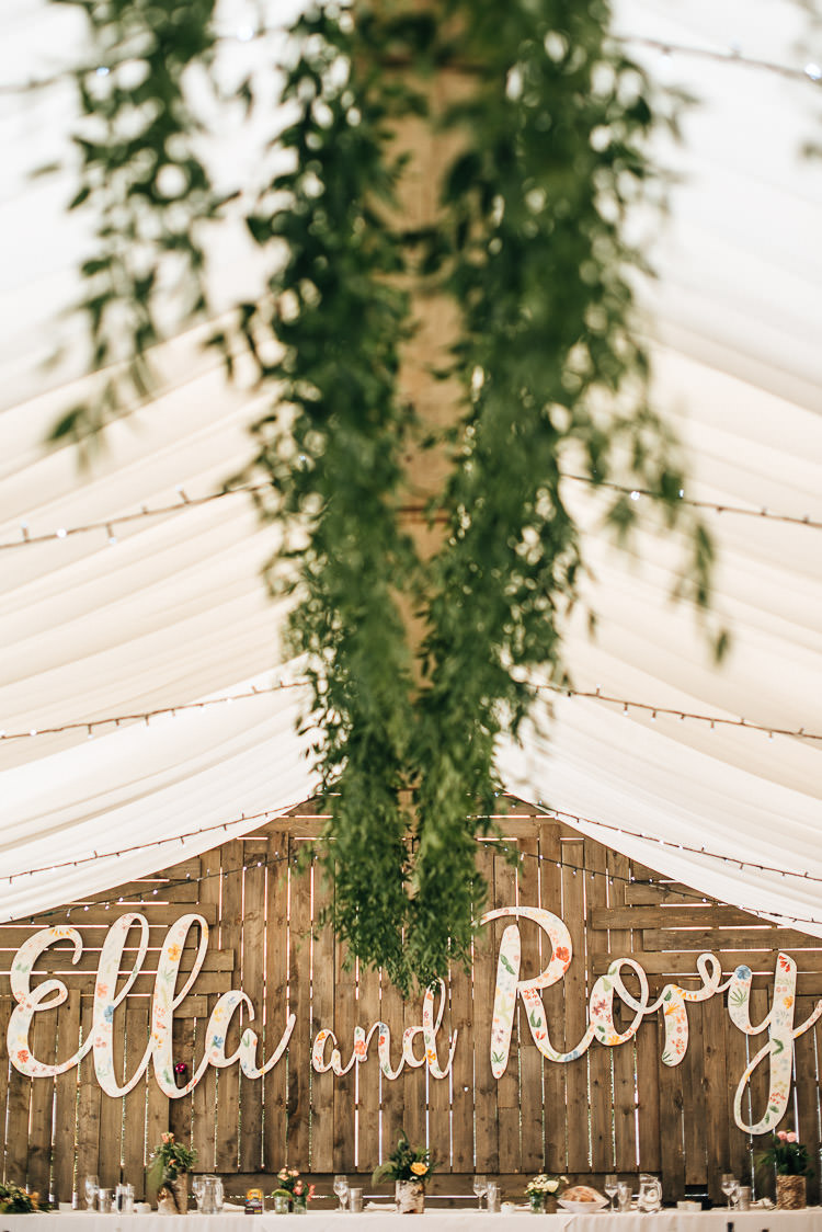 Marquee Greenery Fairy Lights Wooden Backdrop Name Decor Festival Bohemian Glamping Wedding https://theshannons.photography/