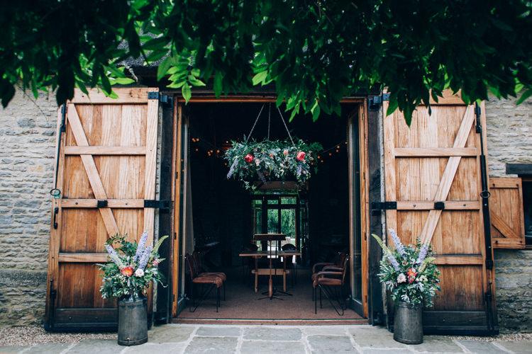 Barn Ceremony Door Flowers Hanging Hoop Churns Flowery Bohemian Secret Garden Wedding https://caseyavenue.co.uk/