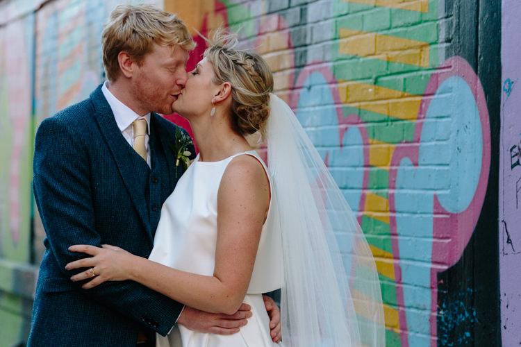 London City Bride Groom Buildings Street Graffiti Wall Kiss Jesus Peiro Dress Navy Suit | Modern Tropical Gold Urban Wedding https://www.christinewehrmeier.com/