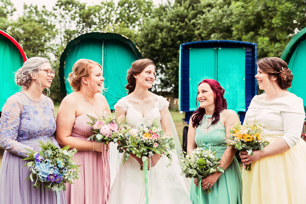 Bride Bridal Bespoke Dress Cape Sweetheart Neckline A Line Lace Bridesmaids Purple Pink Green Yellow Wildflower Meadow Bouquet Festival Wedding Mismatched Country Camilla Lucinda Photography