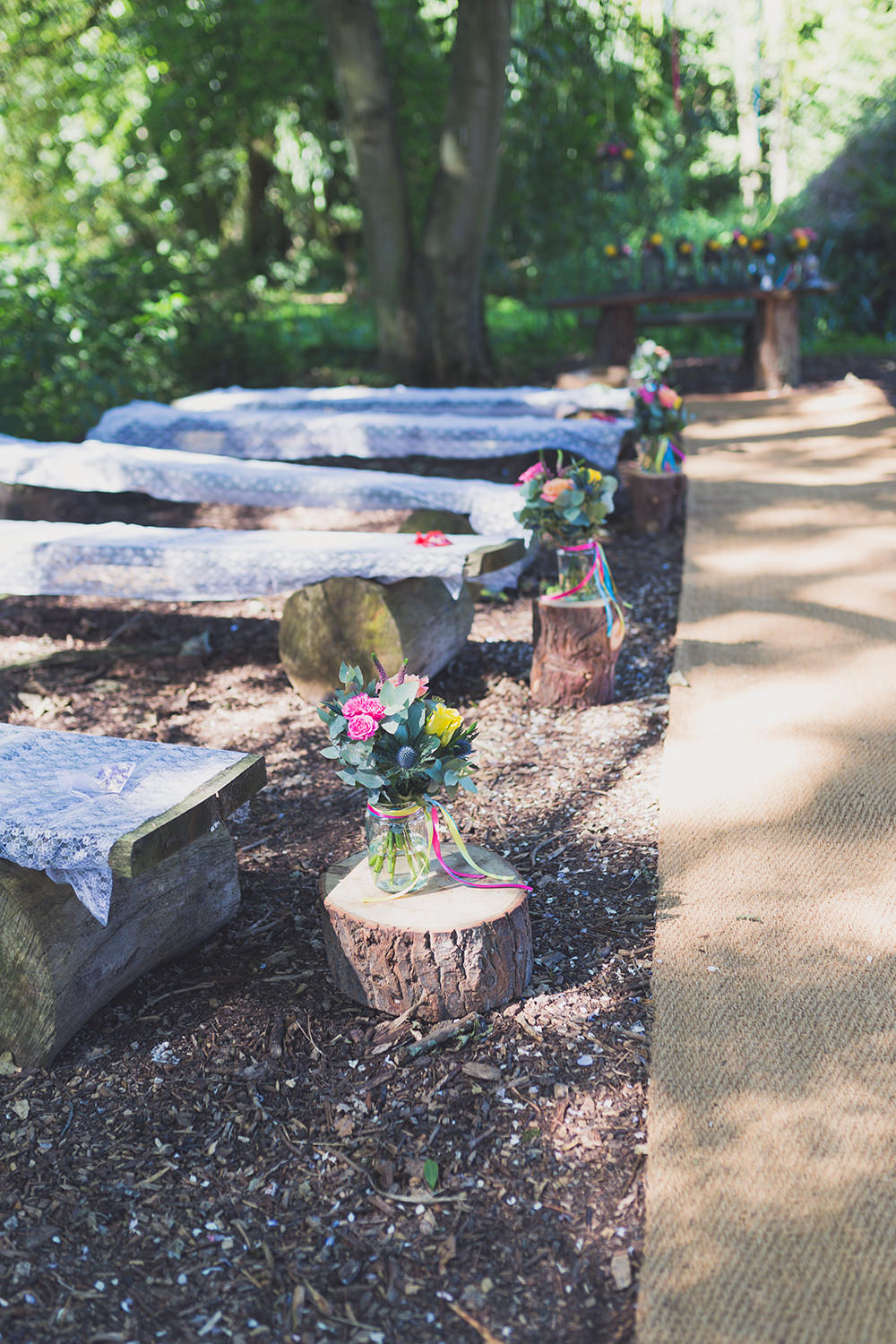 Outdoor Ceremony Wooden Benches Flowers Decor Aisle Flowers Vase Colourful Ribbons Log Stumps Hothorpe Hall Woodlands Wedding Lucy Long Photography