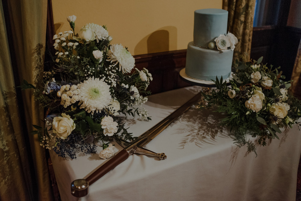 Forest Trees Castle Loch Simple Decor Greenery Fairy Lights Garland Runner Table Blue White Cake Sword | Intimate Winter Outdoor Scotland Wedding Christopher Ian Photography