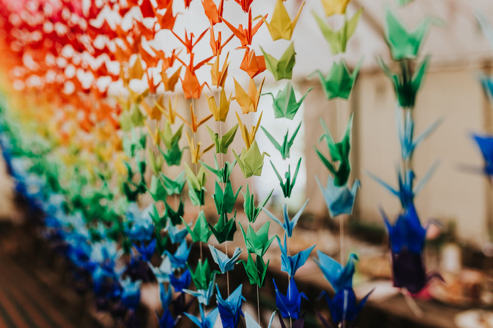 Keeper and The Dell Boho Farm Field Marquee DIY Alternative Rustic Reception Hanging Rainbow Origami Cranes | Relaxed Outdoor Wedding with 1000 Rainbow Origami Cranes Dan Biggins Photography