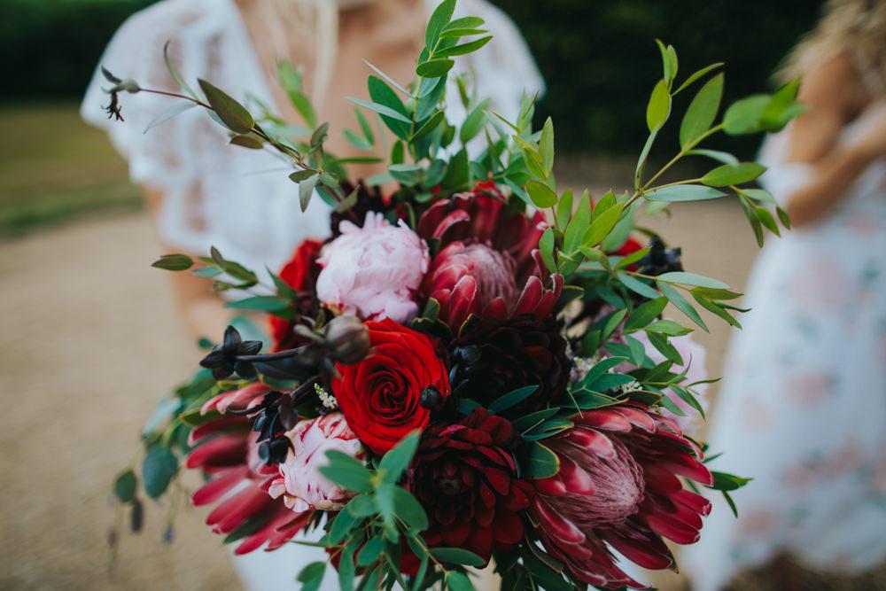 Bouquet Flowers Bride Bridal Red Greenery Foliage Ribbons Peony Peonies Rose Proteas Pink Godwick Great Barn Wedding Joshua Patrick Photography
