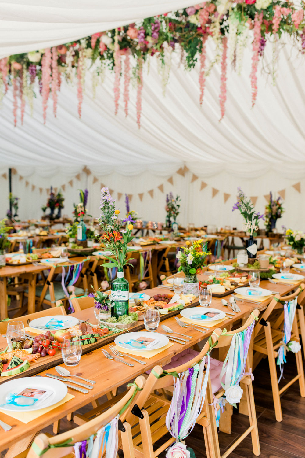 Multicoloured Flowers Floral Hanging Installation Gin Bottles Ribbon Back Chairs Spring Cottage Rivington Wedding Emma B Photography