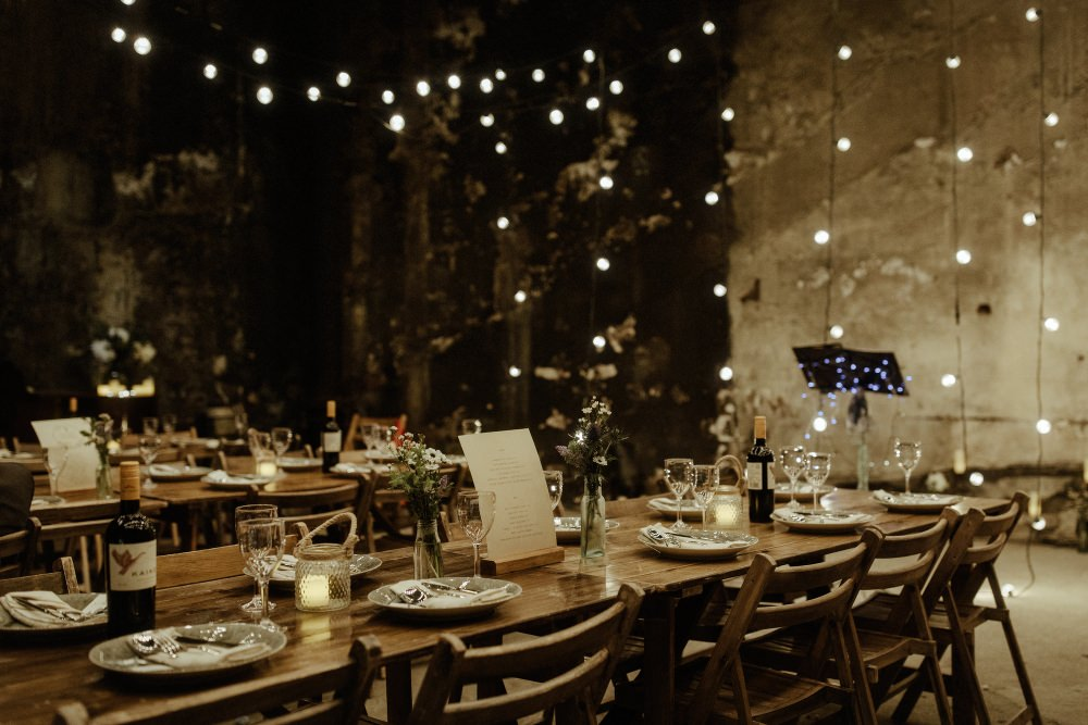 Long Wooden Tables Chairs Flowers Bottles Festoon Lights Lighting Brunel Museum Wedding Olivia and Dan Photography