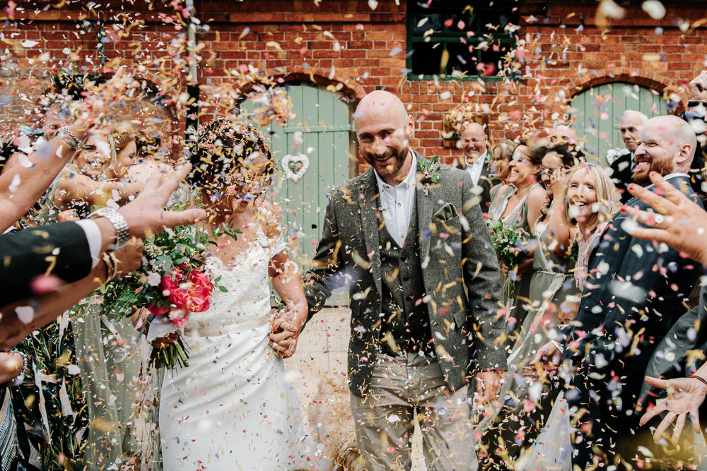 Bride Bridal Dress Gown Lace Detail Drop Cold Shoulder Ribbon Bow Sleeveless Tweed Suit Waistcoat Groom Floral Veil Confetti Stanford Farm Wedding Andy Griffiths Photography