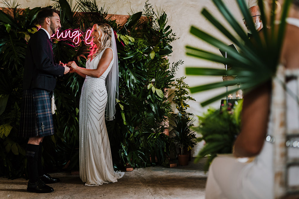 Bride Bridal Beaded Embellished V Neck Dress Gown Succulents Bouquet Kilt Groom Neon Young Love Sign Greenery Backdrop Tropical Luxe Wedding Burfly Photography