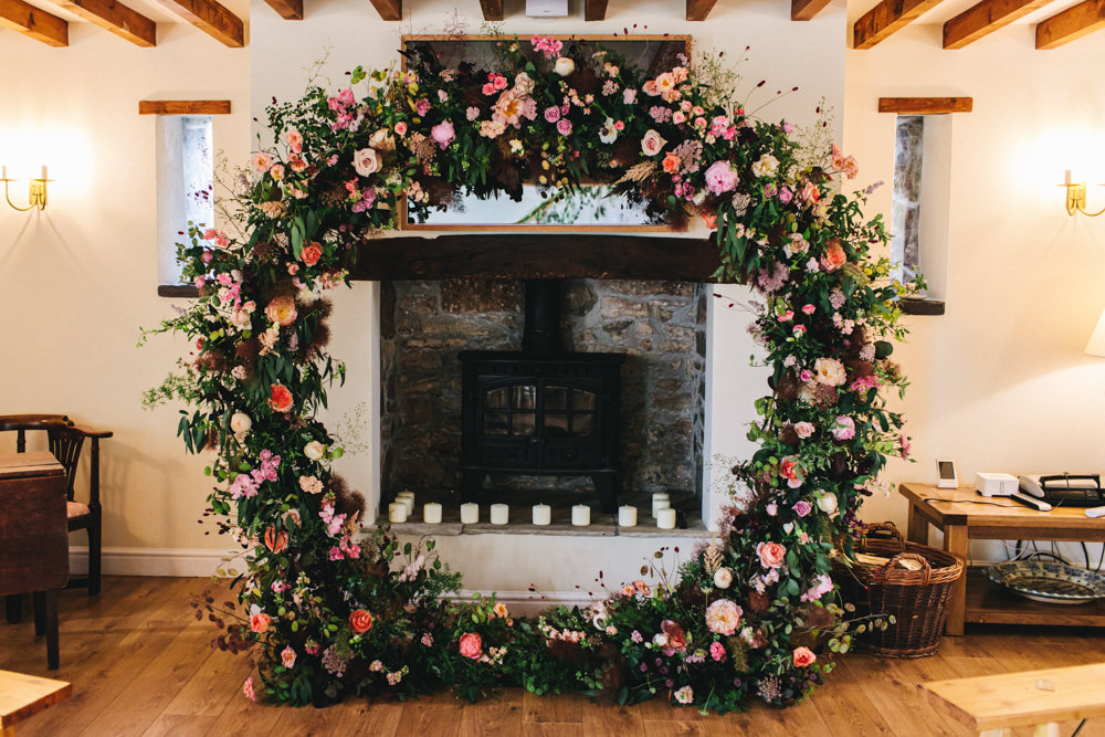 Moon Gate Flower Arch Ceremony Aisle Flowers Greenery Foliage Sweetpeas Freesias Peony Rose Burgundy Pink Outbuildings Wedding Jessica O'Shaughnessy Photography