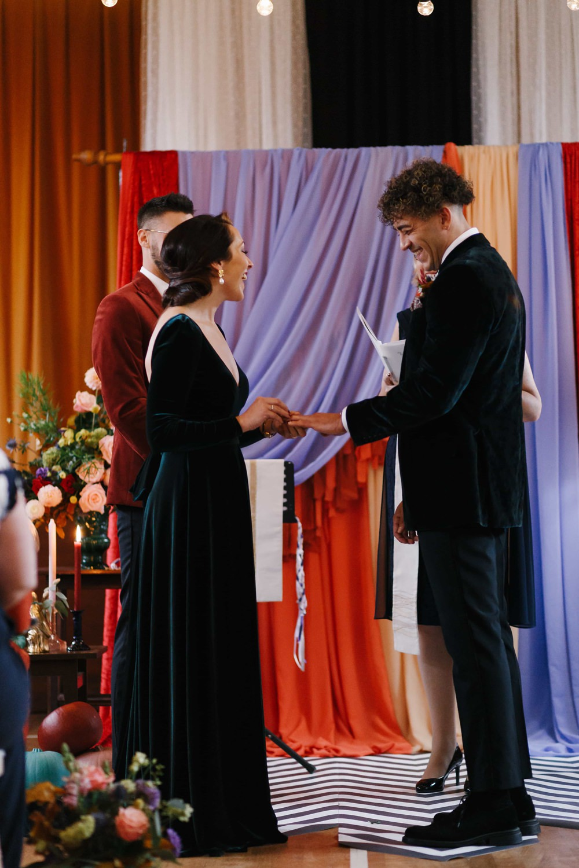 Ceremony Backdrop Drapes Fabric Monochrome Rug Festoon Lights Flowers Village Hall Wedding Emily + Katy Photography