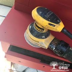 using dewalt sander to distress the red desk