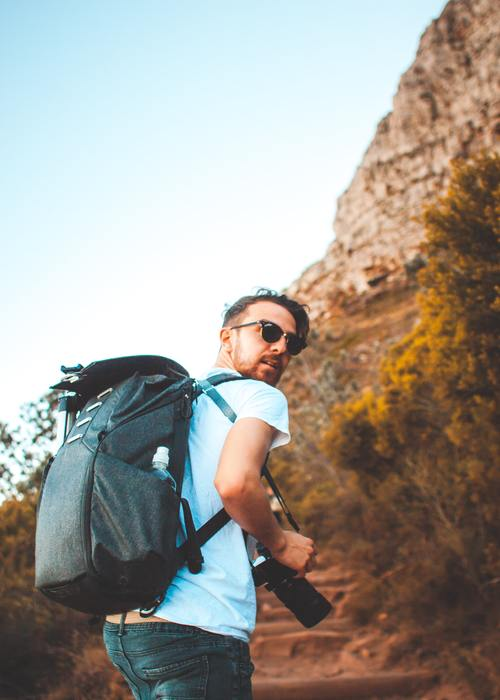 Man carrying a Minimalist Travel Backpack on a hiking trail.