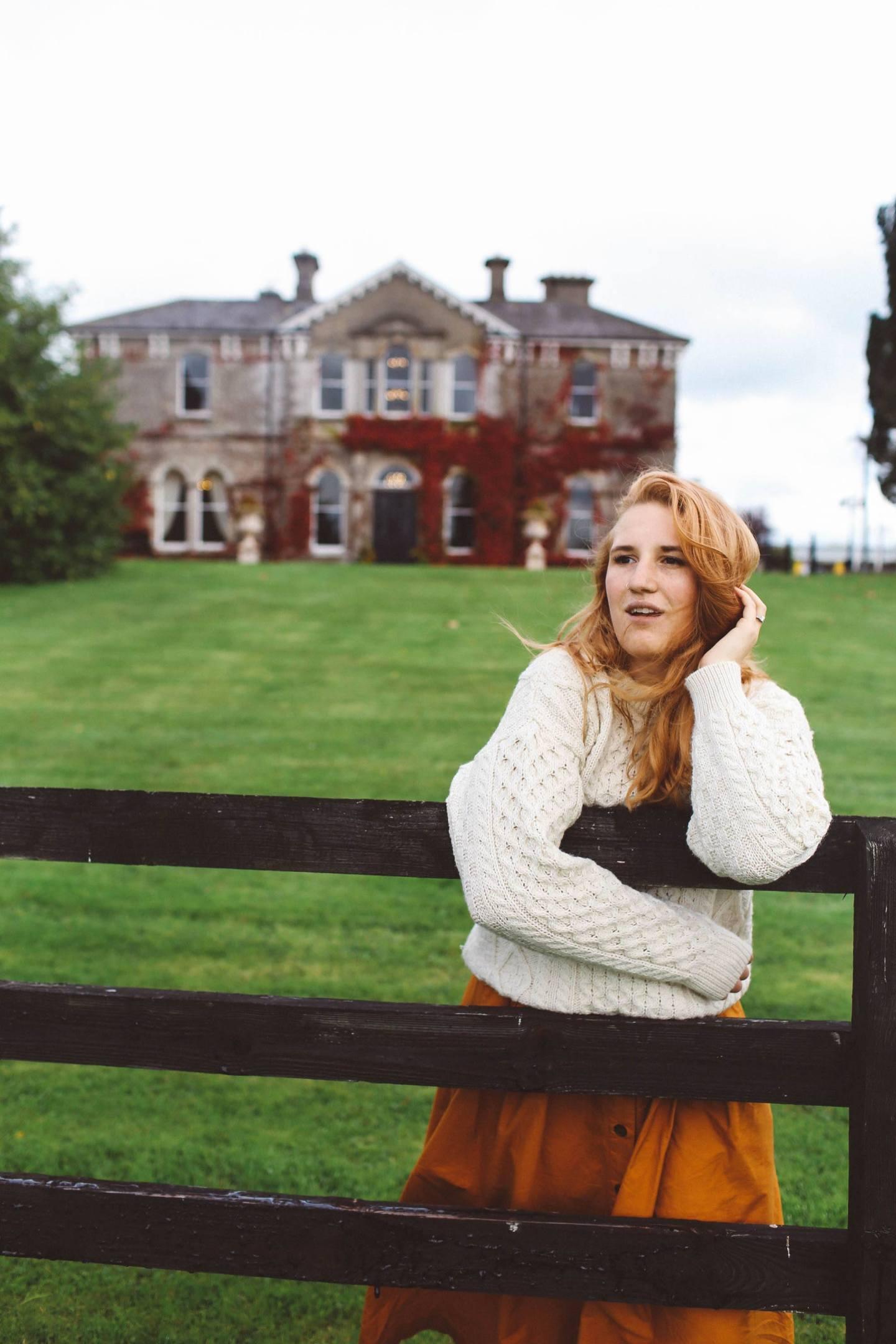 woman white sweater orange midi skirt ireland lyrath estate