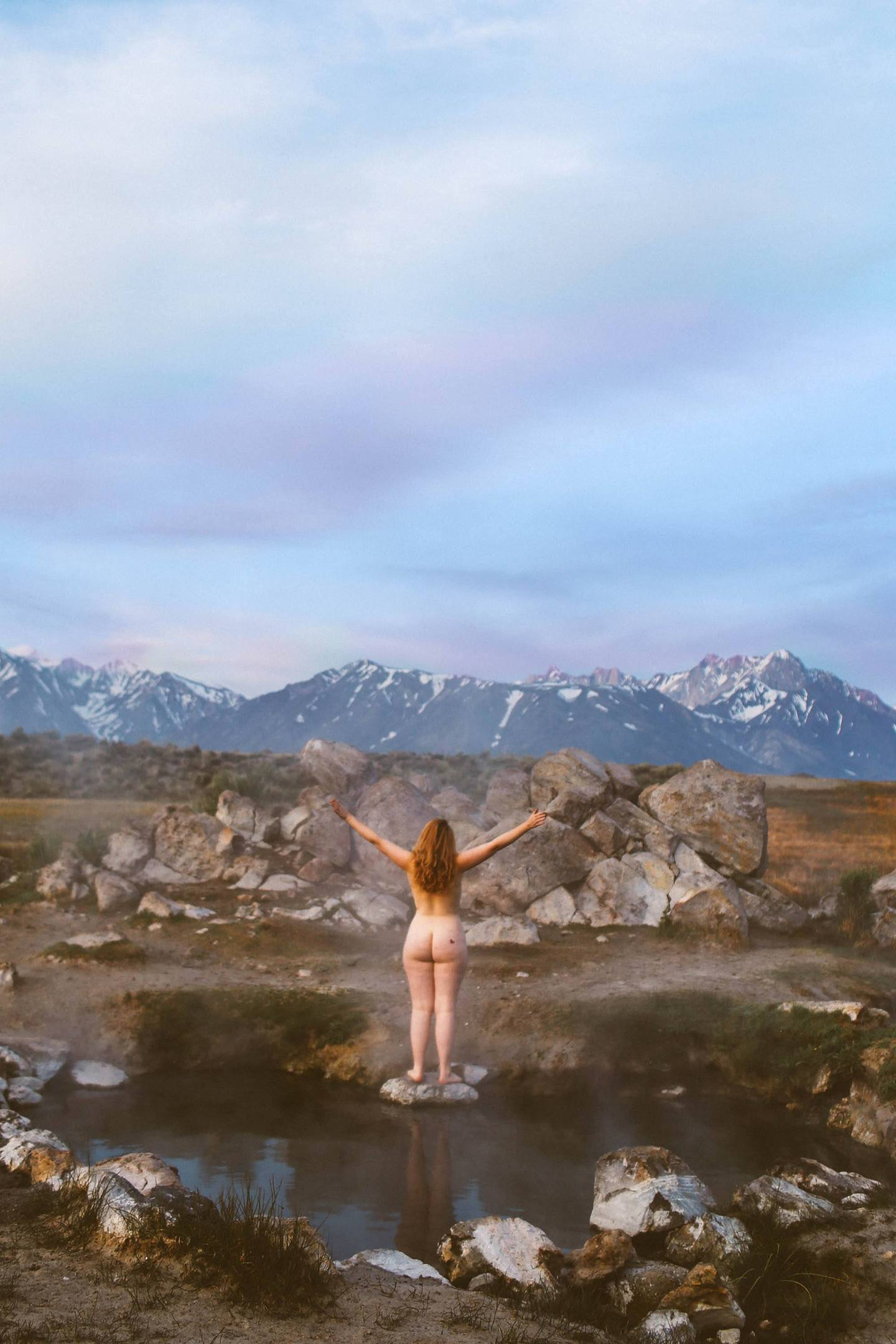 Woman standing naked on rock in a hot spring with snow capped mountains in the background