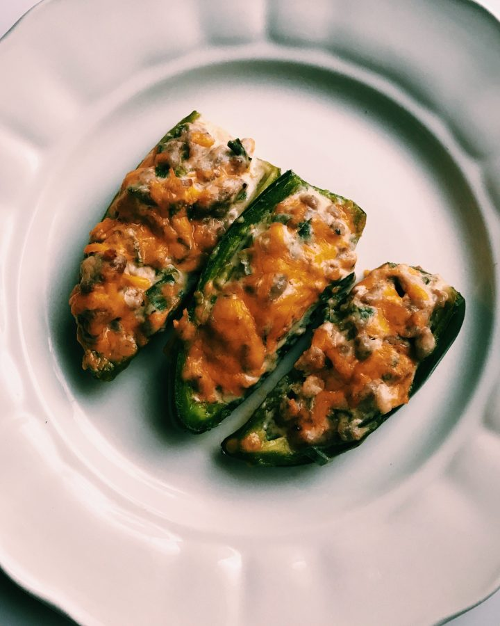 jalapeno poppers with sausage and cheese on a white plate