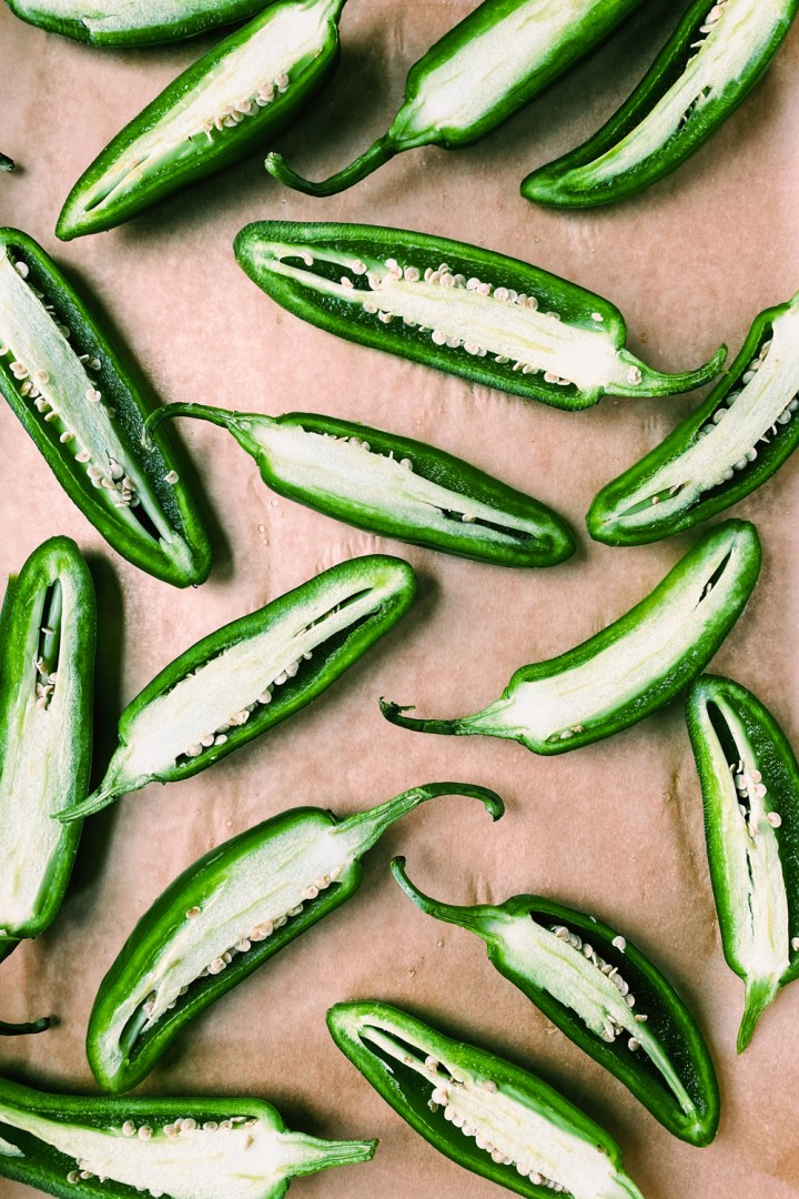 fresh jalapeno peppers halves resting in a baking sheet with brown parchment paper