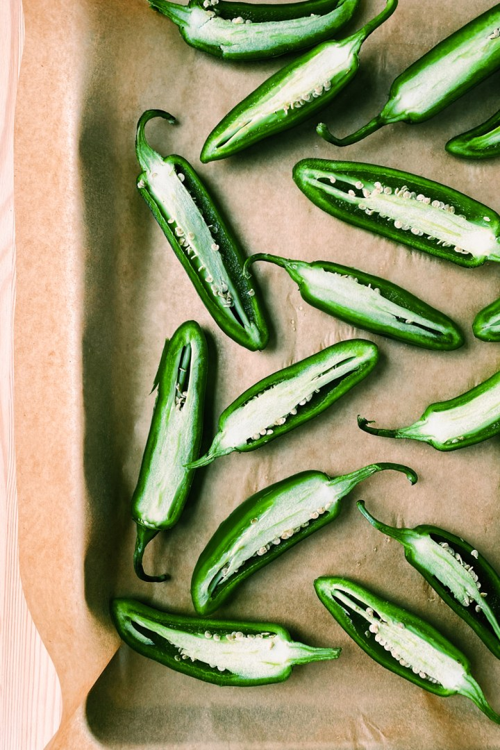 jalapenos halves laying cut side open on a parchment paper lined baking sheet