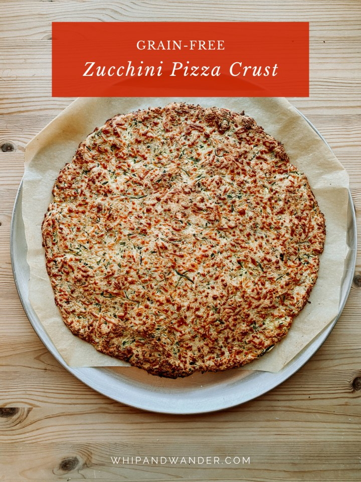 a baked zucchini pizza crust on a round metal baking pan