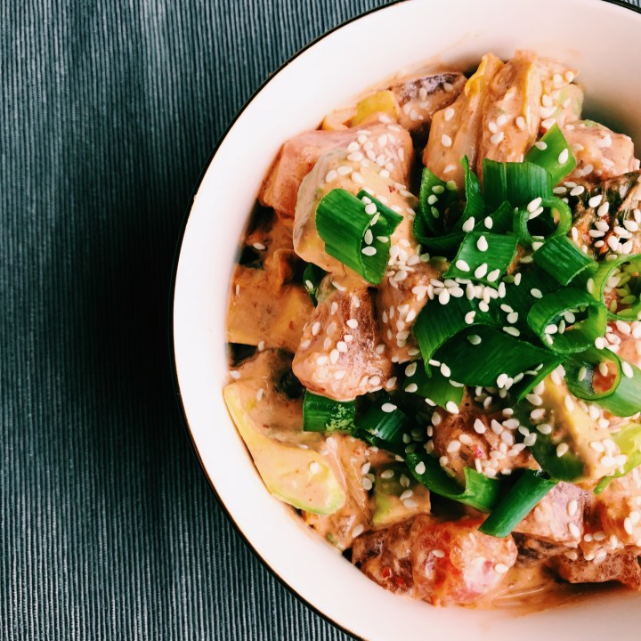 closeup of bowl of ahi kimchi poke with scallions and sesame seeds