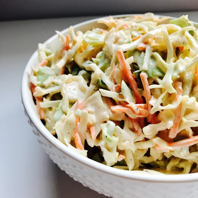 close-up of spicy cabbage slaw in a white bowl on a neutral background