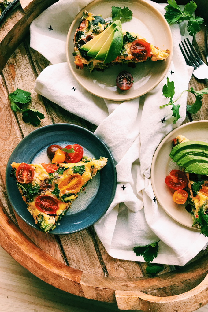 a wooden serving board with several plates of kitchen sink frittata and cilantro and a white towel