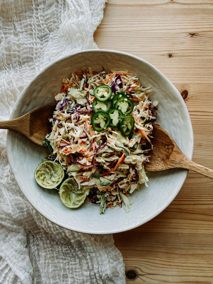 wooden salad servers resting in a white dish filled with spicy cabbage slaw, topped with limes and jalepenos