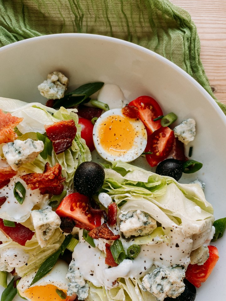a jammy egg, tomatoes, and black olives on top of a wedge salad