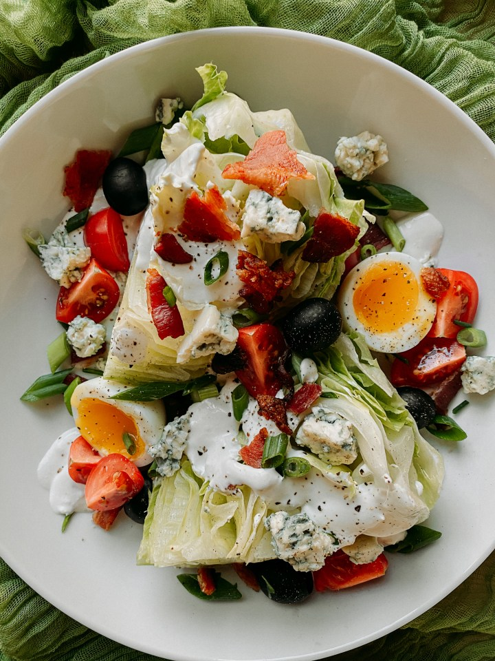 wedges of iceberg lettuce topped with eggs, tomatoes, blue cheese, bacon, and green onions