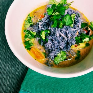 curry, vegetables, cilantro, and purple cauliflower in a white bowl on a teal background